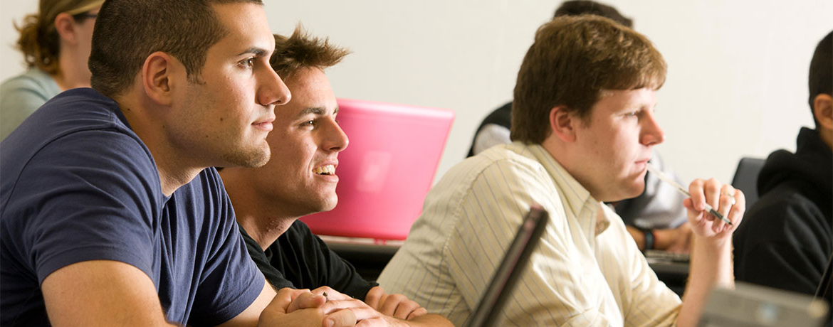 students smiling while listening to a lecture